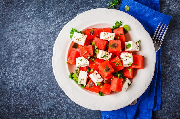 Watermelon salad with feta cheese and herbs in a white plate on blue background, top view.