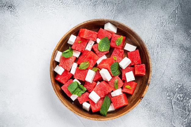 木の板にフェタチーズを添えたスイカのサラダ。白色の背景。上面図。