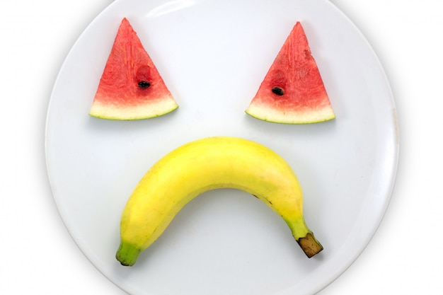 Watermelon slice and banana sad faces on white plate on white background
