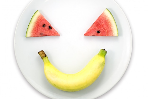 Watermelon slice and banana smiling faces on white plate