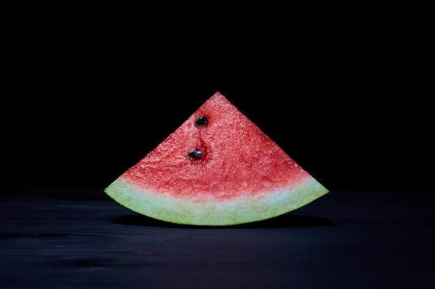 Watermelon slice closeup on a black