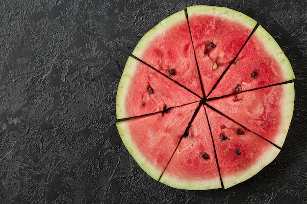 Watermelon slice on dark stone table.