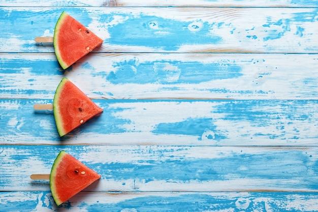 Фруктовое мороженое ломтик арбуза на синем деревянном фоне