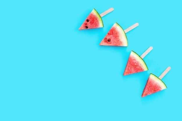 Popsicles ломтик арбуза на синем фоне.