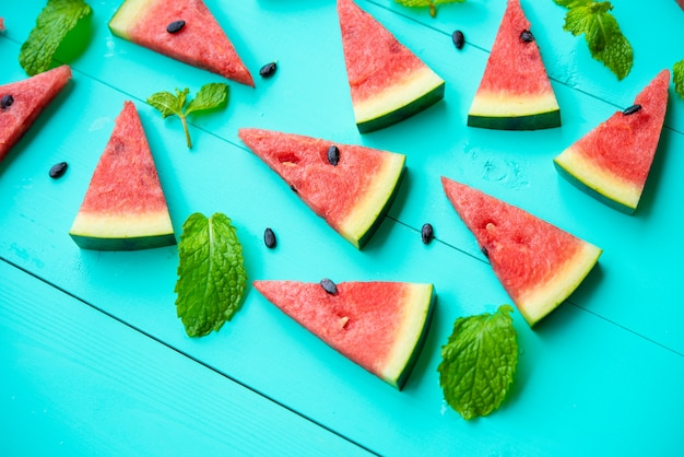 Watermelon slice with mint leaves on blue table