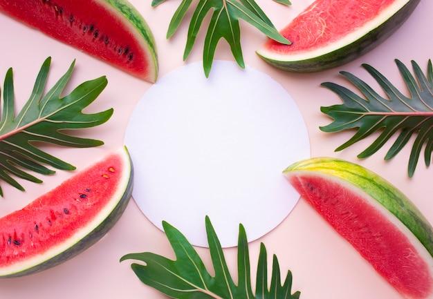 パステルカラーの背景にxanaduの葉とスイカのスライス。夏のフルーツのコンセプトのアイデア。フラットレイデザイン