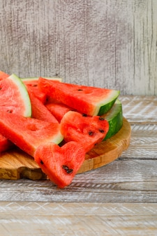 Watermelon slices on a cutting board on wooden and grunge background. side view.
