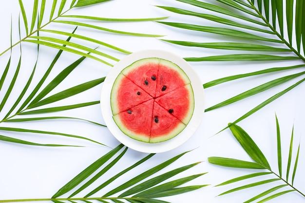 白い表面に熱帯のヤシの葉の白い皿にスイカのスライス。上面図