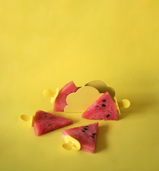 노란색 배경에 아이스크림 스틱에 수박 조각. 창의적인 아이디어 평면도