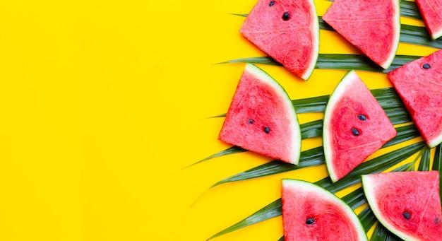 黄色の背景に熱帯のヤシの葉にスイカのスライス。夏の背景コンセプト