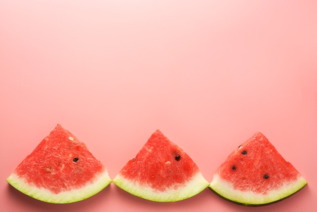 Watermelon slices pink background