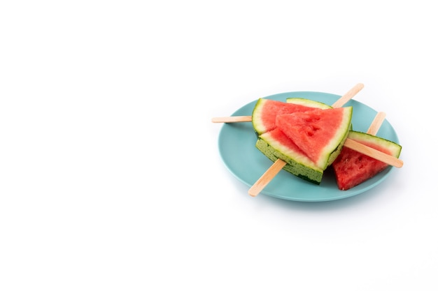 Watermelon slices popsicles on blue plate isolated on white