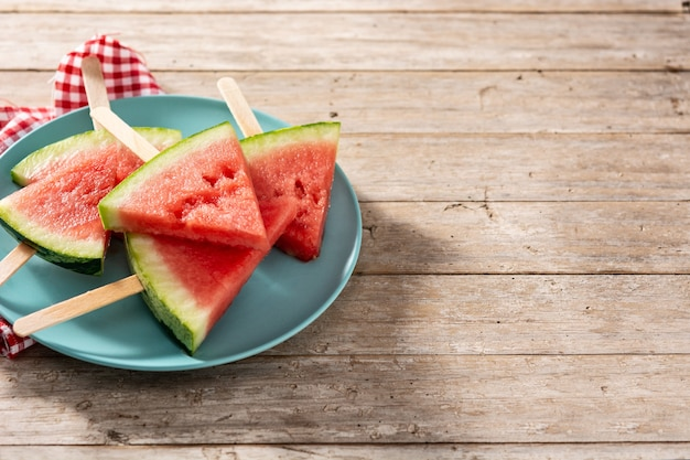 Watermelon slices popsicles on blue plate on rustic wooden table