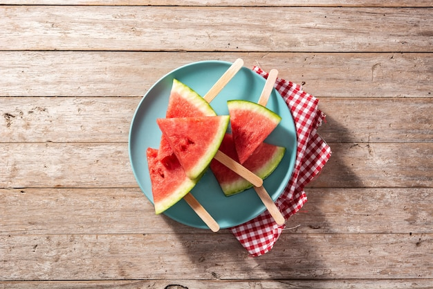 Watermelon slices popsicles on blue plate and wooden table