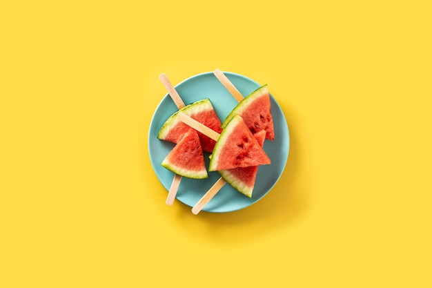 Watermelon slices popsicles on blue plate and yellow.