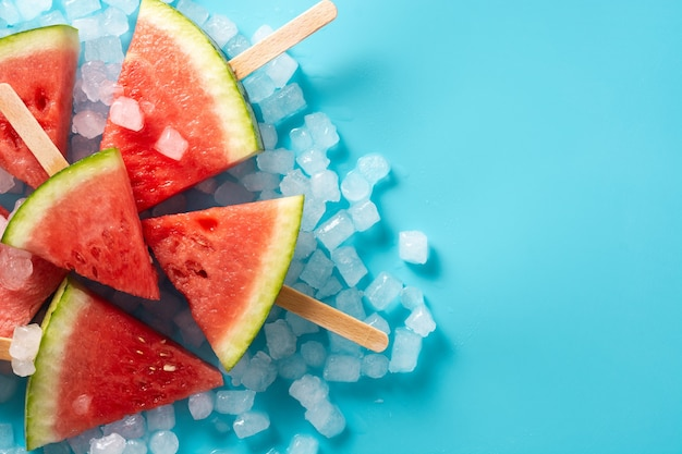 Watermelon slices popsicles and ice on blue surface