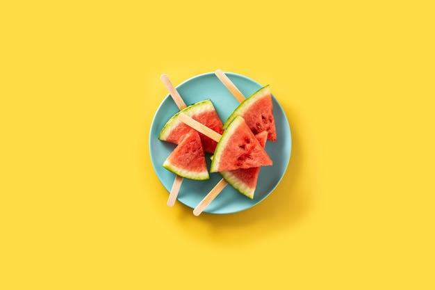 Фруктовое мороженое ломтиками арбуза на синей тарелке и желтом.