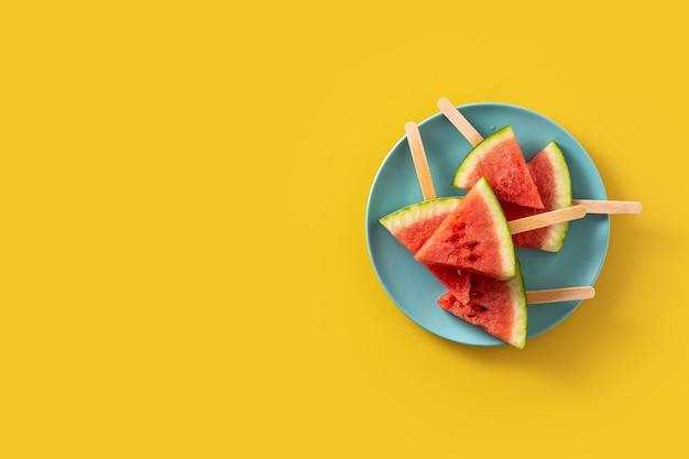 スイカは黄色い表面でアイスキャンディーをスライスします