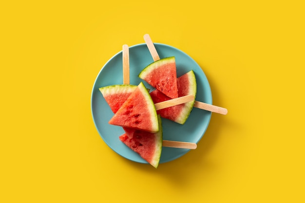 Watermelon slices popsicles on yellow surface