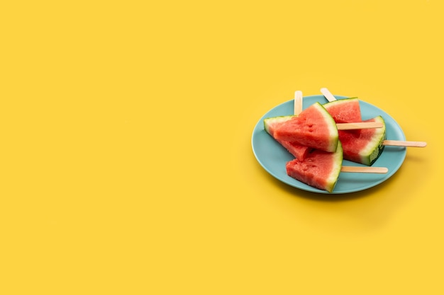 Watermelon slices popsicles on yellow