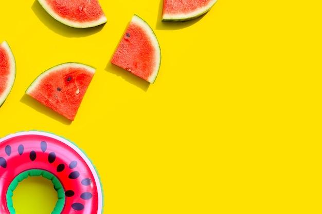 黄色の背景に膨脹可能なリングが付いているスイカのスライス。夏の背景コンセプト