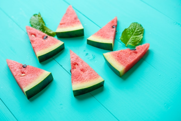Watermelon slices with mint leaves on blue table