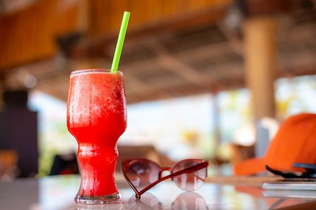 빨대가 있는 유리에 수박 스무디, 테이블 위에 서 있고, 여름날 청량 음료