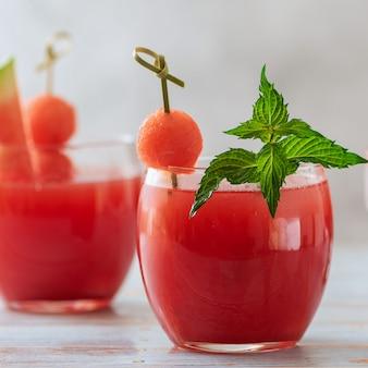Арбузный смузи в стакане с ломтиками свежего арбуза на светлом фоне