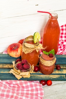 Watermelon smoothie in a jar with peach, lime