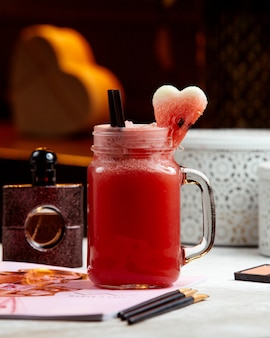 Watermelon smoothie in mason jar garnished with heart shaped watermelon