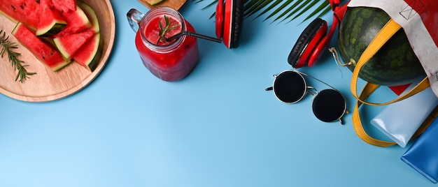 Watermelon smoothie  and traveler accessories on blue background.