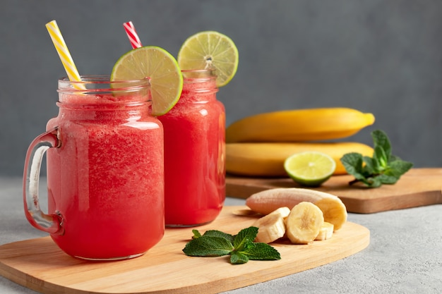 Watermelon smoothie with banana, lime and mint in mug jars