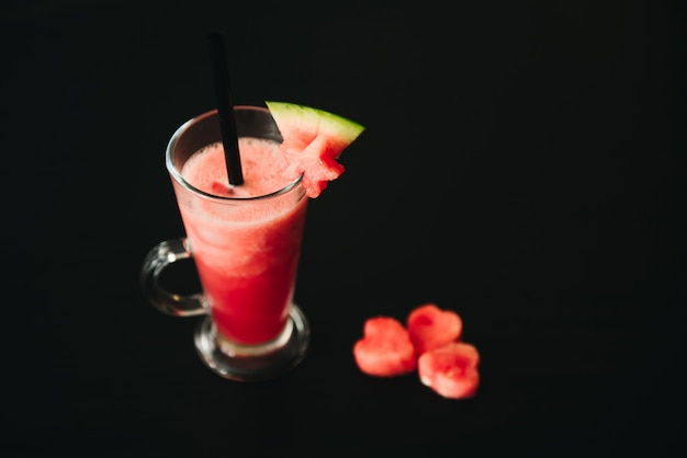 Watermelon smothie and slices with lime on black