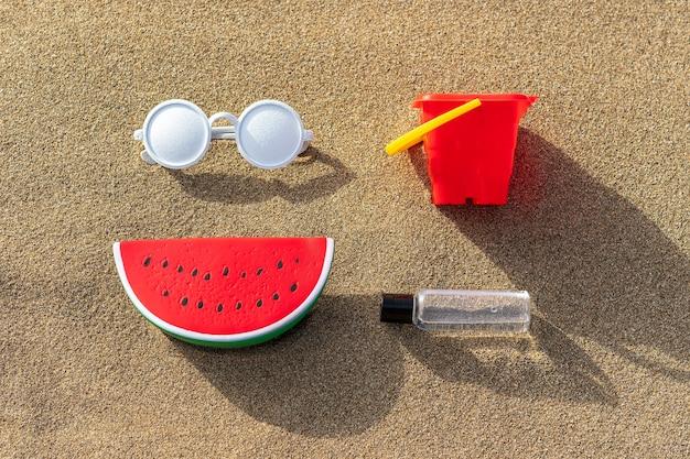 砂の上のサングラスをかけたスイカのおもちゃ