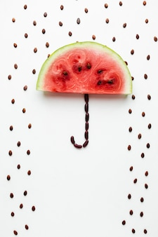 Watermelon umbrella with seeds on white background