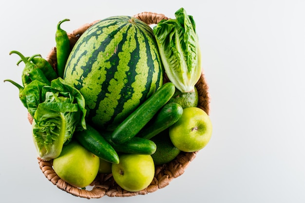 Watermelon in a wicker basket with lettuce, apple, cucumber, avocado, peppers on a white table