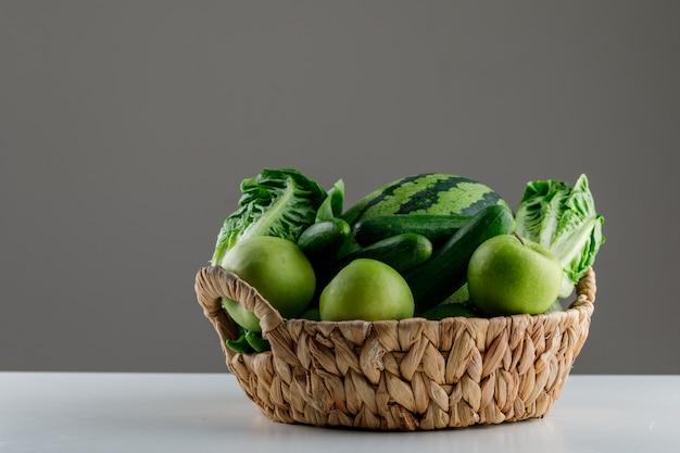 Арбуз с листьями салата, яблоко, огурец в плетеной корзине на белом и сером столе