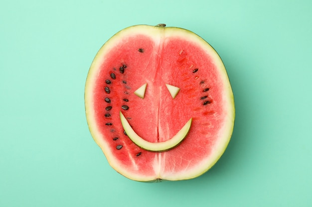 Watermelon with smiley face on mint space, top view