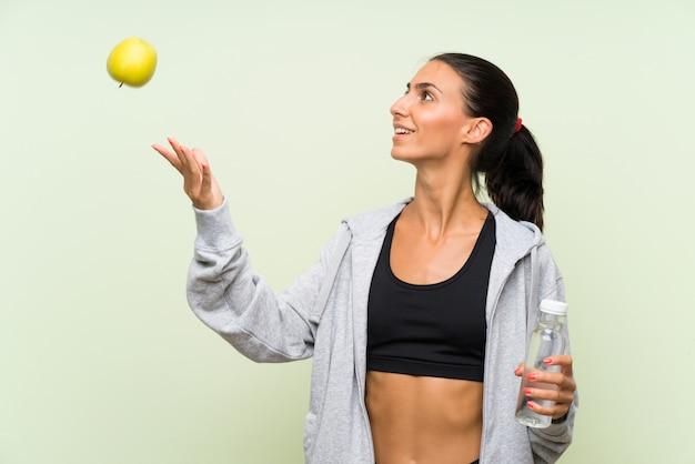 リンゴとwaterover分離された緑の壁のボトルを持つ若いスポーツ女性