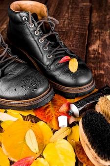 秋の紅葉と木製の背景に防水黒ブーツ