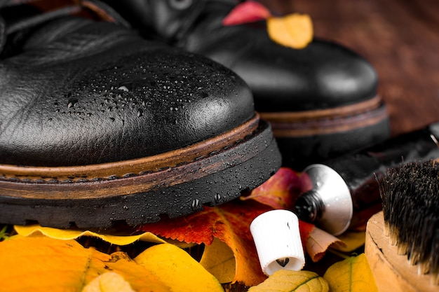 Waterproof black boots with autumn leaves polishing equipment