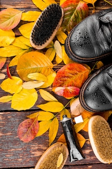 Waterproof black boots on wooden surface with autumn leaves polishing equipment,