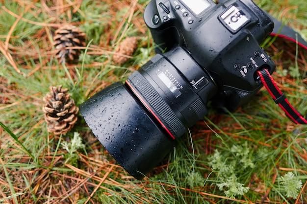 緑の草に雨滴と防水デジタル一眼レフ写真カメラ