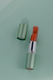Waterproof red lipstick on a green background