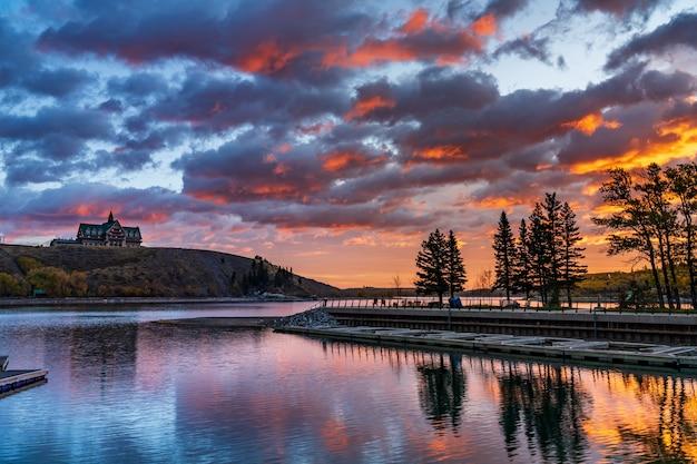 단풍 시즌에 새벽에 waterton 호수 국립 공원 호숫가. 푸른 하늘, 아름다운 불 구름이 일출 시간에 거울처럼 호수 수면에 반영됩니다. 캐나다 앨버타의 랜드 마크.