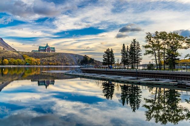 단풍 시즌 아침에 워터 튼 호수 국립 공원 호숫가. 푸른 하늘, 화려한 구름이 일출의 거울처럼 호수 표면에 반영됩니다. 가을 색 풍경. 캐나다 앨버타의 랜드 마크