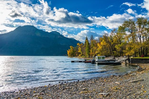 Катер уотертон мидл лейк запускает в осенний сезон листвы солнечного дня утром. национальный парк уотертон-лейкс, альберта, канада.