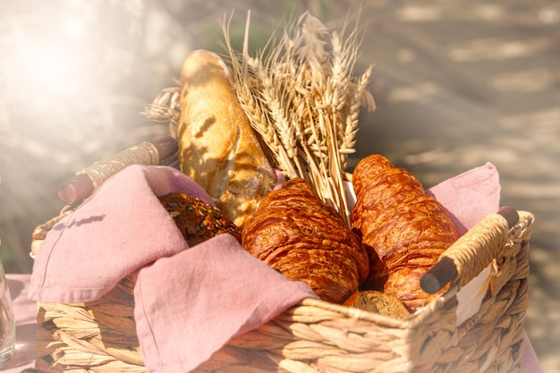 Wattled basket with bread croissant and wheat outside in sunny summer day