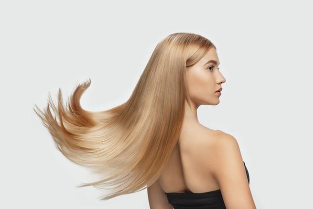 Волна красивая модель с длинными гладкими развевающимися светлыми волосами на фоне белой студии