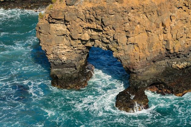 海の岩に砕ける波、洞窟岩。海洋海岸の岩層。テネリフェ島、スペイン